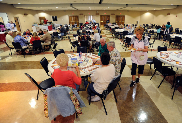 Server Carol Scavetta, right, delivers plates to diners during the weekly fish fry at St. Viator Catholic Church on Friday, March 28, 2014. (David Becker/Las Vegas Review-Journal)