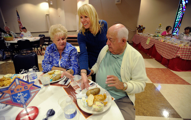 Karen Liguori, center, serves plates of fish and potatoes to Delores Davis and Joe Carr during the weekly fish fry at St. Viator Catholic Church on Friday, March 28, 2014. (David Becker/Las Vegas  ...