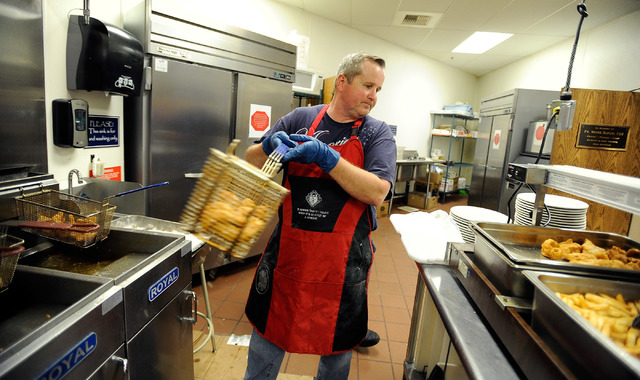 Scott Davis unloads a batch of fried fish after being cooked during the weekly fish fry at St. Viator Catholic Church on Friday, March 28, 2014. (David Becker/Las Vegas Review-Journal)