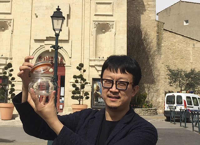 In this photo taken on March 29, 2014, Beijing artist Liang Kegang collects fresh air in the commune of Forcalquier in Provence, France. The jar of air is a piece of conceptual art to protest his  ...
