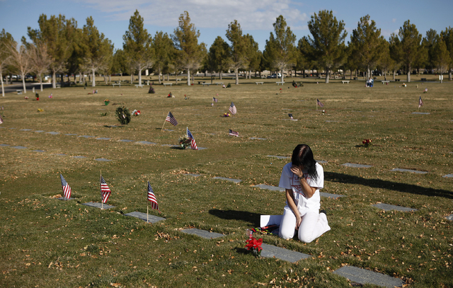 Rondha Gibson kneels at the grave of her husband Stanley Gibson at the Southern Nevada Veterans Memorial Cemetery in Boulder City, Nev. Thursday, Dec. 12, 2013. Gibson was killed by a Las Vegas po ...