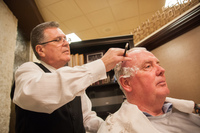 Hair stylist John Taddio, left, shaves the head of Las Vegas Assemblyman John Hambrick at the South Point Barber Salon inside the South Point hotel-casino in November. The assemblyman shaved his h ...