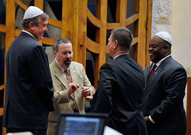 Assemblyman Cresent Hardy, R-Mesquite, left, moderator  Alan Stock, Leo Bletnitsky, president of the Republican Jewish Coalition and Niger Innis look at a coin before it is  is tossed to determine ...