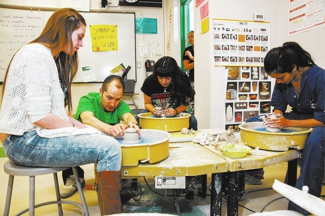 High School Ceramics teacher, Fernando Agreda, second from left, demonstrates proper technique in wheel throwing clay bowls to his student Gina Biscardi, 16, left, as his other students from cente ...