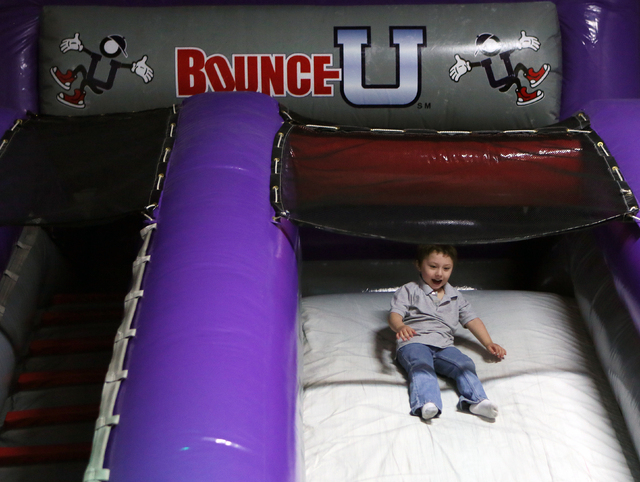 Maddox Long, 4, slides down a slide at Bounce U Monday, March 31, 2014, in Henderson. Bounce U, located at 1000 Stephanie Place, Suite 14, offers a variety of indoor bouncing obstacles as well as  ...