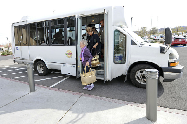 Edith Brown, 87, left, and Imelda Aguirre, 69, right, exit the Henderson Senior Transportation Program bus as they arrive at the Senior Center on Racetrack Road in Henderson. The city is facing a  ...