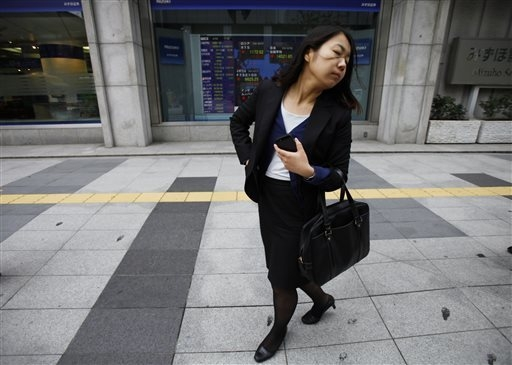 A woman walks by an electric stock board outside a securities firm, Friday, April 18, 2014 in Tokyo. Asian stocks were mostly higher Friday after mixed U.S. earnings reports with most of the regio ...