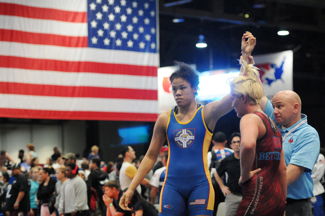 Referee James Stinson, center, holds up the hand of Shai Mason, left, in victory against her opponent Deanna Bettleman during the Asics Open Wrestling Championships at the Las Vegas Convention Cen ...
