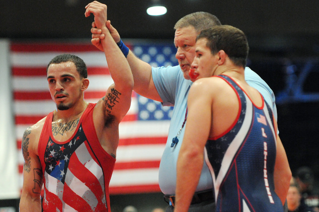 Referee Albert Williams, center, holds up the hand of Jordan Oliver, left, in victory against his opponent Logan Stieber in the Asics Open Wrestling Championships at the Las Vegas Convention Cente ...