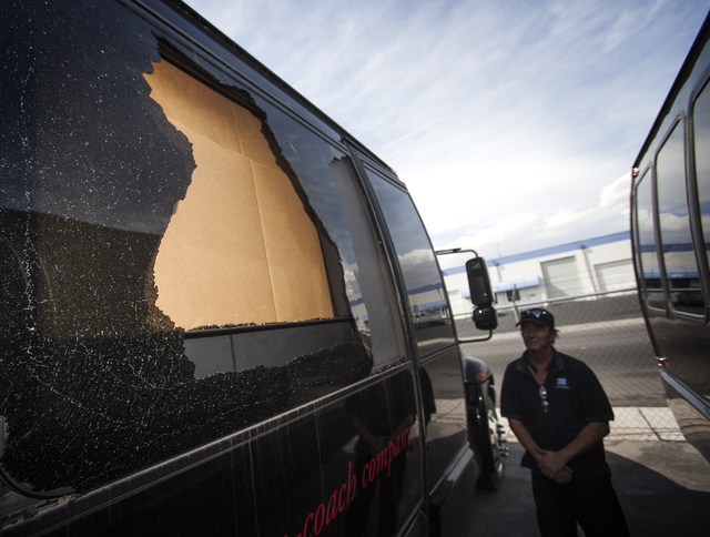 Norm Bemister, shop manager for AWG Ambassador, stands beside a vandalized coach limo at the company's facility at W. Tompkins Avenue and Valley View Road on Friday. The window of the coach was sh ...