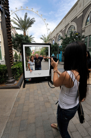 Tourists use a prop from the Polaroid Fotobar while they are photographed at The LINQ on Sunday, April 27, 2014. (David Becker/Las Vegas Review-Journal)