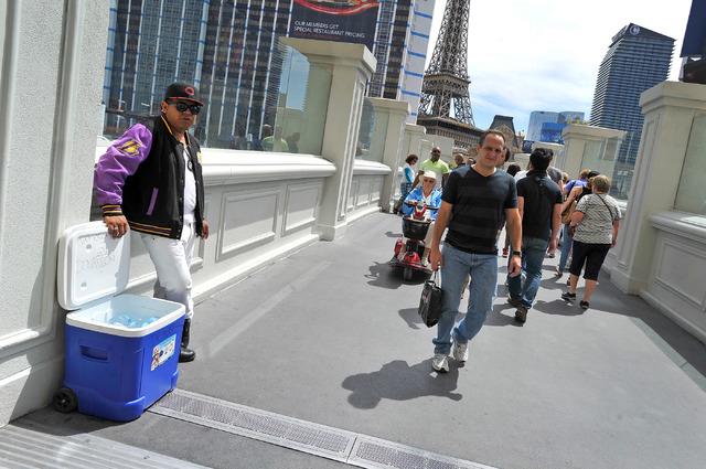A vendor sets up his water stand along a pedestrian bridge near Bally's hotel-casino on Sunday, April 27, 2014. (David Becker/Las Vegas Review-Journal)