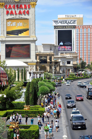 Tourists walk along the Strip in front of Caesars Palace hotel-casino on Sunday, April 27, 2014. (David Becker/Las Vegas Review-Journal)