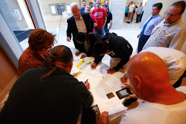 People sign in for a meeting on zoning and licensing procedures for people interested in dispensing, distilling, testing or growing medical marijuana at Las Vegas City Hall on Tuesday (Chase Steve ...