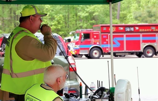 Search and rescue workers assist in the search Monday, April 28, 2014, for a father and his two children who haven't been heard from sending out a text Saturday that they were lost in the vast woo ...