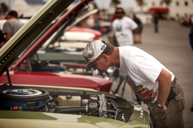Curtis Baker views the engine compartment of a 1969 Ford Mustang during a car show at the Las Vegas Motor Speedway on Friday, April 18, 2014. Car enthusiasts from around the world attended the 50t ...