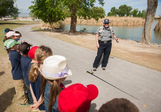 Conservation Educator Ivy Santee, top, of the Nevada Department of Wildlife, instructs first grade students from Pinecrest Academy in Henderson, Nev., how to fish at Floyd Lamb Park at Tule Spring ...