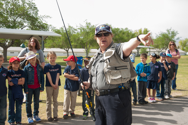 Conservation Educator Ivy Santee, center, of the Nevada Department of Wildlife, instructs first grade students from Pinecrest Academy in Henderson, Nev., how to fish at Floyd Lamb Park at Tule Spr ...