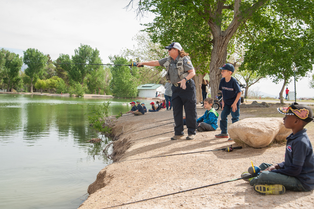 Conservation Educator Ivy Santee, center, of the Nevada Department of Wildlife, instructs first grade students Bryson Rood, 6, standing, from Pinecrest Academy in Henderson, Nev., how to fish at F ...