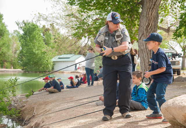 Conservation Educator Ivy Santee, center, of the Nevada Department of Wildlife, instructs first grade students Bryson Rood, 6, from Pinecrest Academy in Henderson, Nev., how to fish at Floyd Lamb  ...