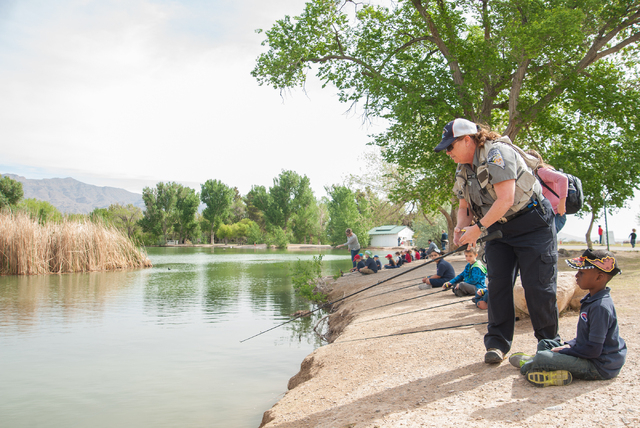 Conservation Educator Ivy Santee of the Nevada Department of Wildlife, instructs first grade students Izaiah Samuels, 7, from Pinecrest Academy in Henderson, Nev., how to fish at Floyd Lamb Park a ...