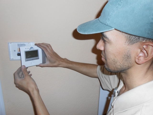 Carlos Perez, field service technician, installs one of NV Energy's new thermostats March 13, 2014 at a northwest Las Vegas home. The thermostats allow customers to program their HVAC units from t ...