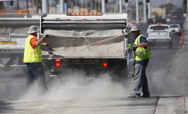Workers spread sand to soak up an oil slick several blocks long on Decatur Boulevard between Vegas Drive and Smoke Ranch Road in Las Vegas Thursday, April 3, 2014.  (John Locher/Las Vegas Review-J ...