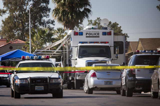 Las Vegas police are seen investigating an officer-involved shooting Tuesday morning at a home in the 5700 block of Maceta Avenue, near Twain Avenue and Duneville Street. A Las Vegas SWAT officer  ...