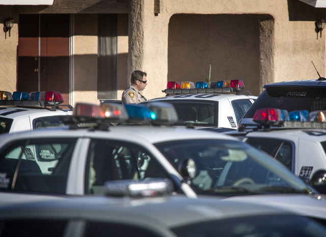 A Las Vegas police officer stands near squad cars on Jicama Street and Twain Avenue on Tuesday. A standoff with an armed suspect resulted in a Las Vegas SWAT officer shooting and killing the man e ...