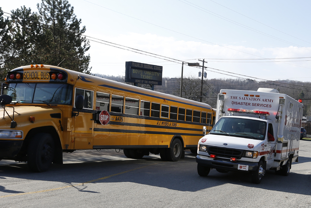 A Salvation Army disaster services vehicle drives past a school bus onto the campus of the Franklin Regional School District where several people were stabbed on Wednesday in Murrysville, Pa., nea ...