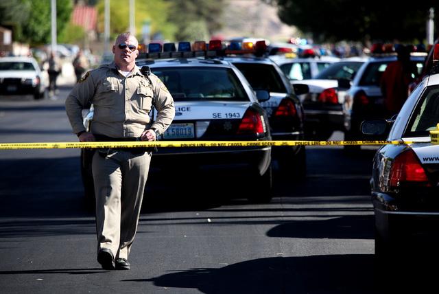 Las Vegas Metropolitan police officer Josh Haynes stands near the scene of a blockade in the 5300 block of Palm Street near Hacienda Avenue in Las Vegas on Tuesday, April 29, 2014. (Justin Yurkani ...