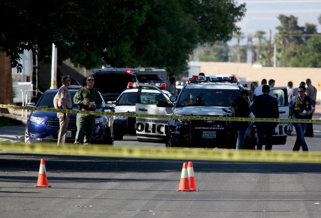 Las Vegas Metropolitan police officers and detectives stand in front of a home that was the scene of an officer involved shooting on the 2300 block of Palm Street near Hacienda Avenue in Las Vegas ...