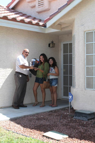 A homebuyer in North Las Vegas receives keys and a welcome move-in bundle from Lenny Chide, left, director at Neighborhood Housing Services of Southern Nevada. (Special to View)