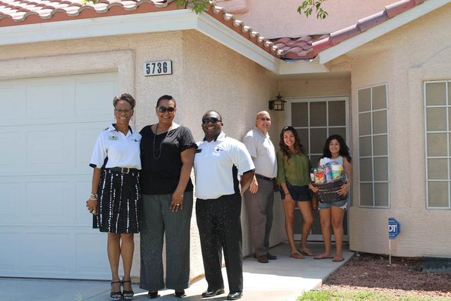 A homebuyer in North Las Vegas receives keys and a welcome move-in bundle from Lenny Chide, third from right, director at Neighborhood Housing Services of Southern Nevada. (Special to View)