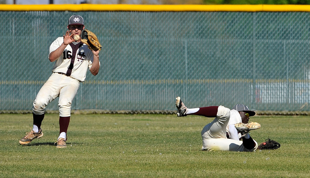 A blooper drops between Cimarron-Memorial outfielders Adam Mitchell, left and Micquel Robinson on Monday against Bishop Gorman. The visiting Gaels won, 4-1. (David Becker/Las Vegas Review-Journal)