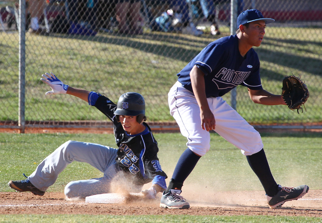 Basic's Skyler Mahoney slides into third base for a triple as Foothill's Tyler Van Stone waits for the relay throw during the sixth inning Thursday at Foothill. Basic won, 5-0. (Chase Stevens/Las  ...