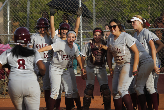 Faith Lutheran's Cheyenne Kidd (8) is greeted at home plate by her teammates after hitting a three-run homer in the sixth inning against Cheyenne on Tuesday. Kidd's shot was one of two homers for  ...