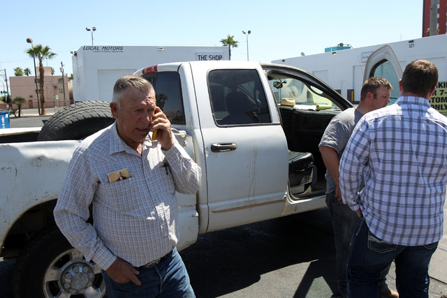 Embattled Bunkerville rancher Cliven Bundy, left, talks on the phone while his son Dave Bundy, second from left, and son-in-law Josh Logue to a reporter on the corner of North Las Vegas Boulevard  ...