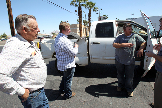 Embattled Bunkerville rancher Cliven Bundy, left, his son Dave Bundy, right, and son-in-law Josh Logue talk to a reporter on the corner of North Las Vegas Boulevard and East Stewart Avenue in down ...