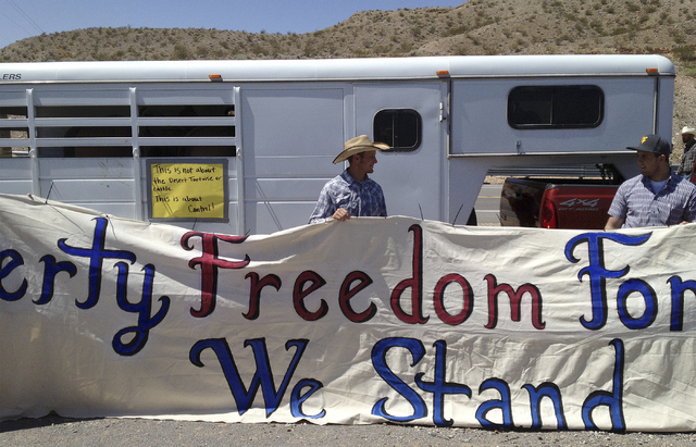 Kolby Hughes, right, and John Banks, left, and Kolby Hughes help hold up a sign in support of rancher Cliven Bundy near Bunkerville, Nev. Monday, April 7, 2014. (John Locher/Las Vegas Review-Journal)