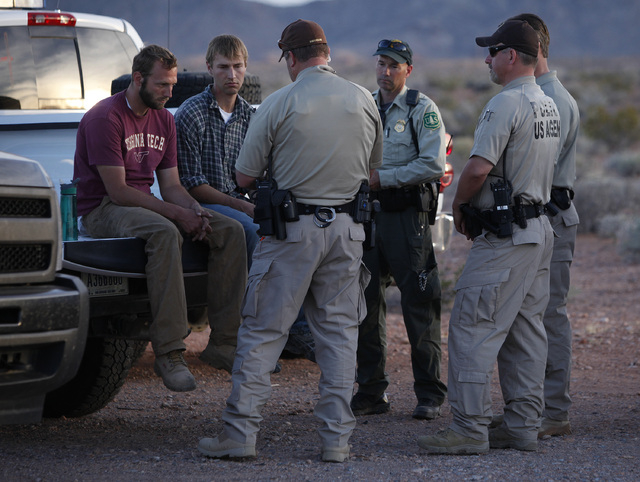 Tyler Shillig, left, and Spencer Shilling sit on a truck before they are released by federal law enforcement officers at the Lake Mead National Recreation Area near Overton, Nev. Thursday, April 1 ...