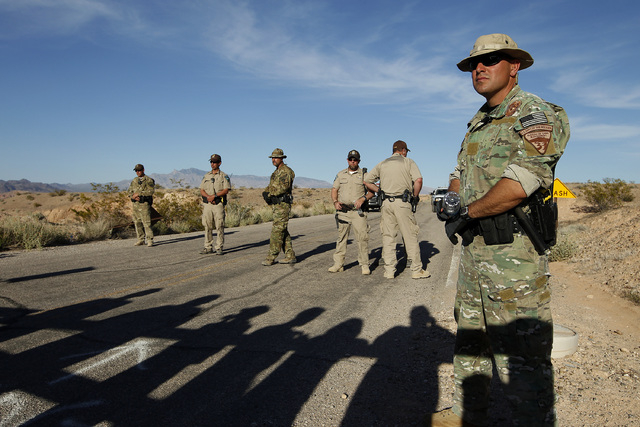 Federal law enforcement officers block a road at the Lake Mead National Recreation Area near Overton, Nev. Thursday, April 10, 2014. In the foreground are the shadows of protestors. Two people wer ...
