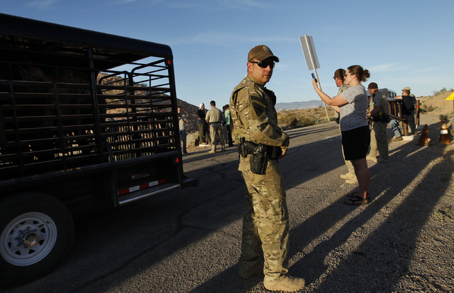 Federal law enforcement officers guard a convoy of cattle at the Lake Mead National Recreation Area near Overton, Nev. Thursday, April 10, 2014. Two people were detained while protesting the round ...