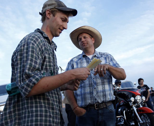 Ammon Bundy, right, talks with Spencer Shillig at the Lake Mead National Recreation Area near Overton, Nev. Thursday, April 10, 2014. Shillig and his brother were detained while protesting the rou ...