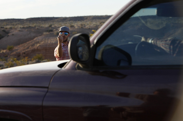 A protestor motions towards a convoy of cattle at the Lake Mead National Recreation Area near Overton, Nev. Thursday, April 10, 2014. Two people were detained while protesting the roundup of cattl ...