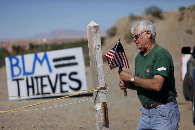 "Jim Olson puts up a flag near what was the Bureau of Land Management's ""first amendment area"" in Bunkerville, Nev. Thursday, April 10, 2014. The Bureau of Land Management removed their t ..."