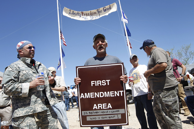 "Charlie Brown holds up a sign from the Bureau of Land Management's ""first amendment area"" during a protest of the Bureau of Land Management's roundup of cattle near Bunkerville, Nev. Thu ..."
