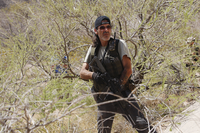 An armed civilian waits nearby in some bushes as the Bundy family and their supporters gather together under the I-15 highway just outside of Bunkerville in order to confront the BLM and demand th ...