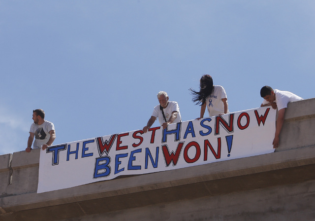 Supporters of the Bundy family hang a sign on the I-15 highway just outside of Bunkerville after the BLM agreed to release the impounded cattle on April 12, 2014. (Jason Bean/Las Vegas Review-Journal)
