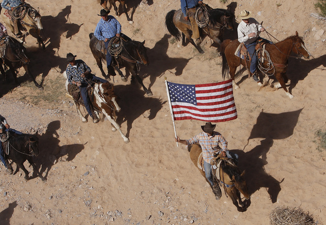 The Bundy family and their supporters fly the American flag as their cattle were released by the Bureau of Land Management back onto public land outside of Bunkerville on April 12, 2014. (Jason Be ...